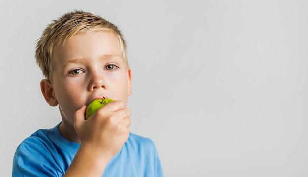 Chico lindo mordiendo una manzana verde