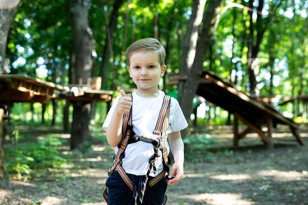 Chico lindo muestra el pulgar hacia arriba con equipo de escalada en un parque de aventuras
