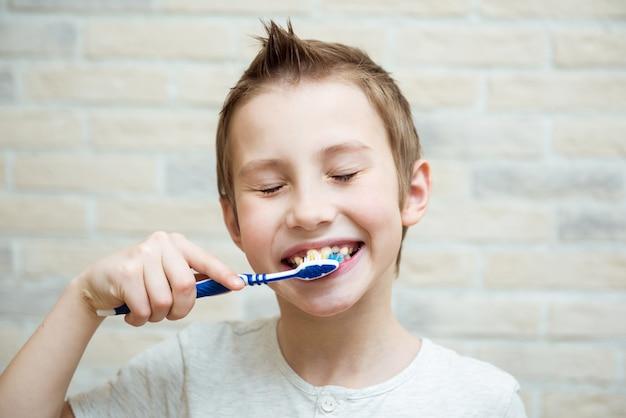Chico lindo muestra sus dientes y cepillo de dientes.