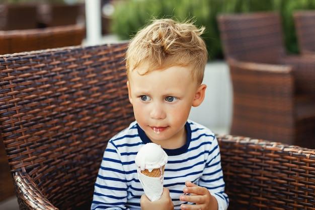 Chico lindo niño comiendo un helado en la terraza