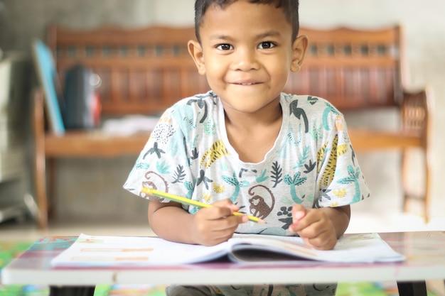 Chico lindo niño estudiando y pensando en casa.