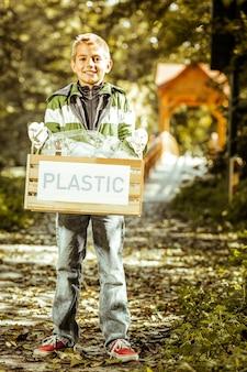 Un chico lindo posando con una caja de arena plástica en un sendero forestal en un buen día