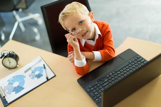 Chico lindo sentado en el escritorio de la oficina y usa computadora