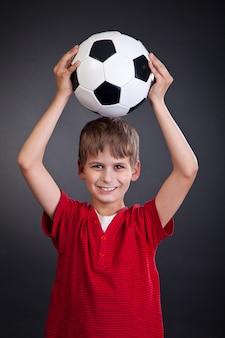 Chico lindo sostiene un balón de fútbol