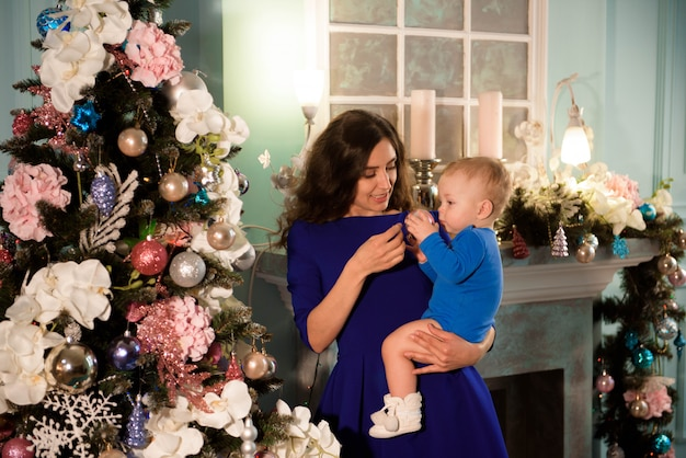 Chico lindo y su madre decorando el árbol de navidad para vacaciones