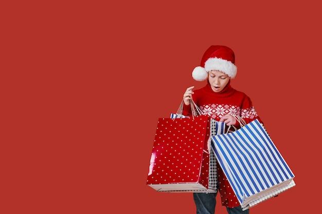 Chico lindo en suéter rojo con bolsas de compras