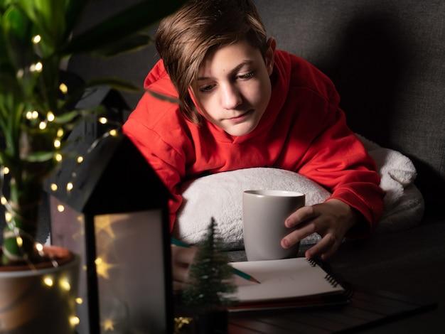 Chico lindo con taza acostado en el sofá y dibujo imagen noche luces y decoraciones navideñas