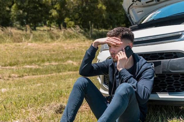 Chico llamando junto a coche averiado