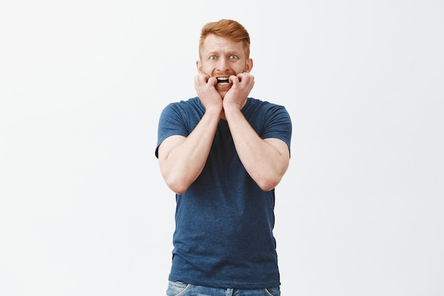 Chico masculino atractivo asustado nervioso y ansioso con cabello pelirrojo, mordiéndose las uñas, mirando asustado