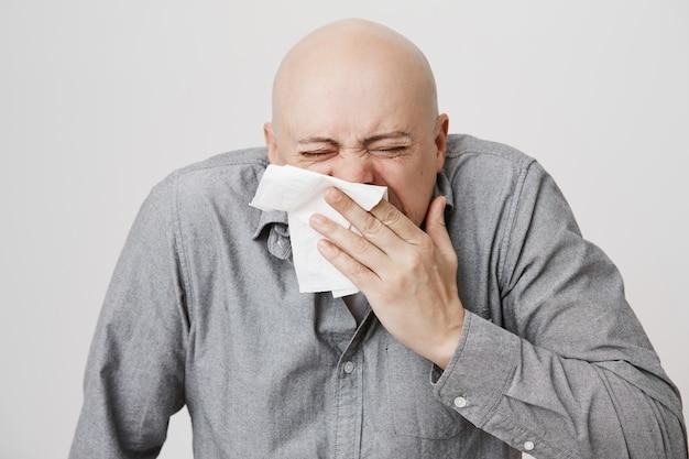 Chico de mediana edad calvo enfermo estornudando en la servilleta