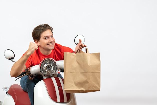 Chico mensajero orgulloso sonriente joven en uniforme rojo sentado en scooter sosteniendo una bolsa de papel en la pared blanca