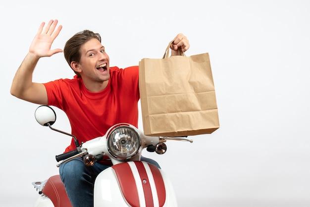 Chico mensajero sonriente joven en uniforme rojo sentado en scooter sosteniendo una bolsa de papel diciendo hola en la pared blanca