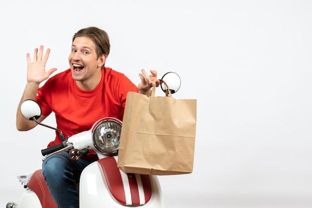 Chico mensajero sonriente joven en uniforme rojo sentado en scooter sosteniendo una bolsa de papel mostrando cinco en la pared blanca