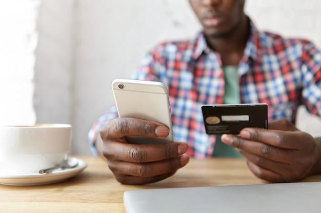 Chico de moda joven sentado en un café con smartphone y portátil