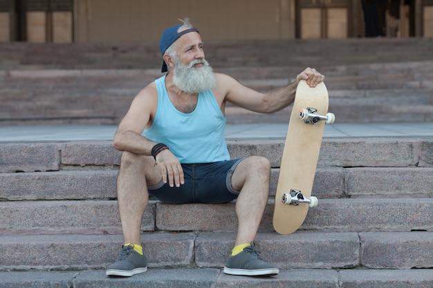 Chico de moda con patineta en la ciudad, relajándose en las escaleras