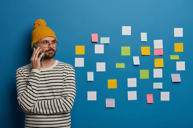 Un chico de moda seguro intercambia ideas creativas con un colega o pareja a través del teléfono celular, desvía la mirada, se para contra un fondo azul con pequeñas notas limpias