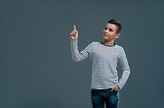 Chico de moda con un suéter a rayas y jeans muestra el pulgar hacia arriba en la idea, un lugar para su publicidad en un gris.