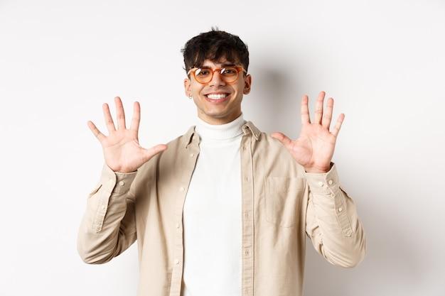 Chico moderno con gafas y traje elegante, mostrando el número de diez dedos y sonriendo, de pie sobre fondo blanco.