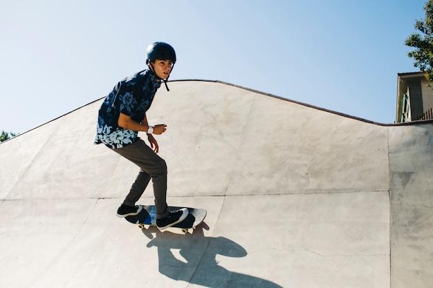 Chico moderno posando durante el patinaje