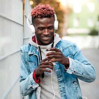 Chico moderno de tiro medio con auriculares y taza de café