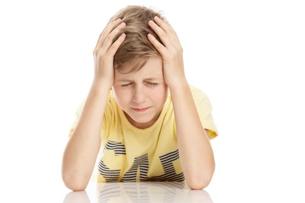 El chico molesto tiene las manos detrás de la cabeza. aislado sobre fondo blanco.