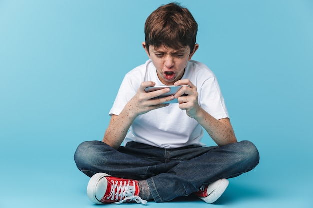 De chico morena caucásico con pecas vistiendo camiseta blanca casual sosteniendo y usando el teléfono inteligente mientras está sentado en el piso aislado sobre la pared azul