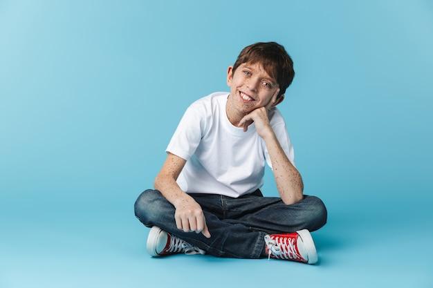 De chico morena europeo con pecas vistiendo camiseta blanca casual sonriendo mientras está sentado en el piso aislado sobre la pared azul