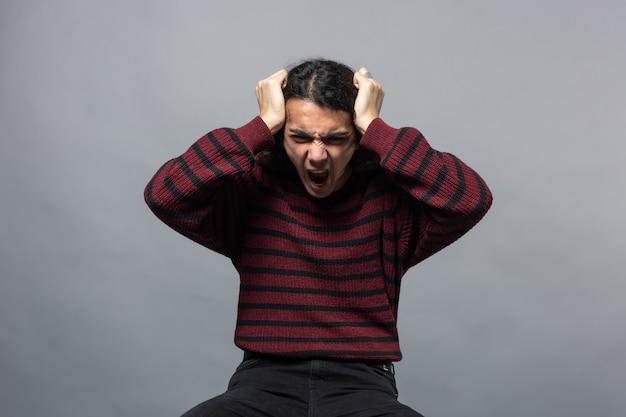 Un chico muestra enojo mientras sostiene su cabeza