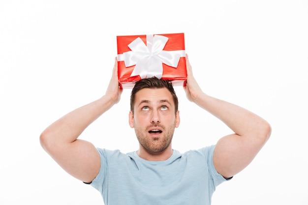 Chico musculoso en casual divirtiéndose y poniendo caja de regalo roja con lazo de cinta en la cabeza