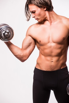 Chico musculoso culturista haciendo ejercicios con mancuernas aislado sobre pared blanca