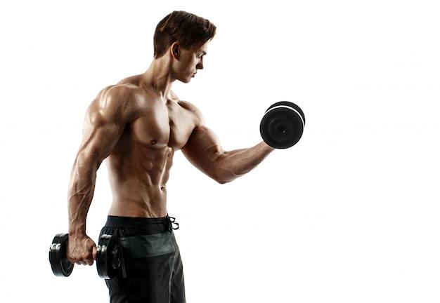 Chico musculoso culturista haciendo ejercicios con pesas sobre fondo blanco
