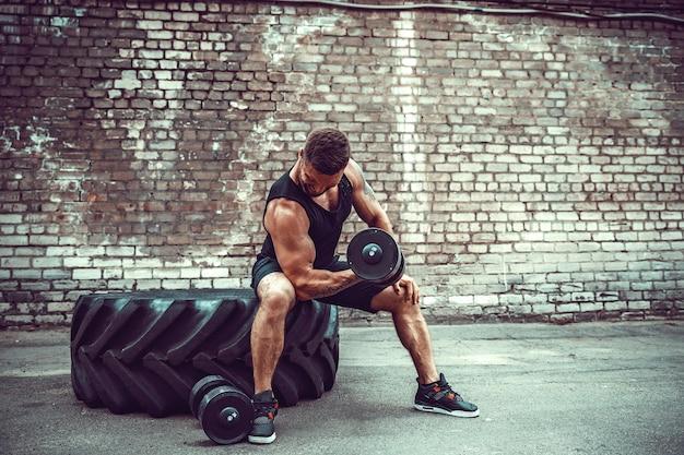 Chico musculoso haciendo ejercicios con pesas contra una pared de ladrillos