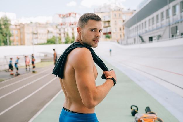 Chico musculoso joven mirando hacia atrás sobre su hombro. retrato de un hombre guapo con pantalones cortos azules.