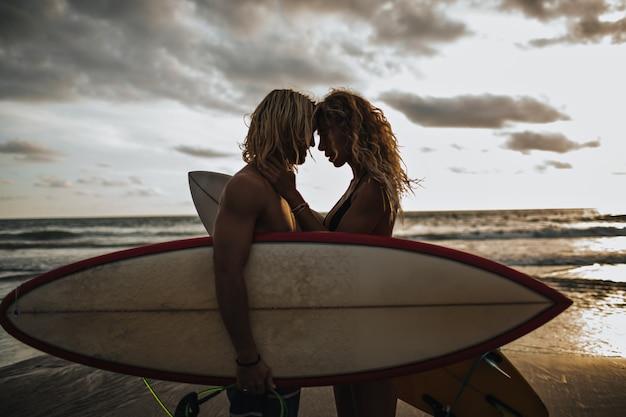 Chico musculoso y su chica delgada se disfrutan. pareja posando con tablas de surf