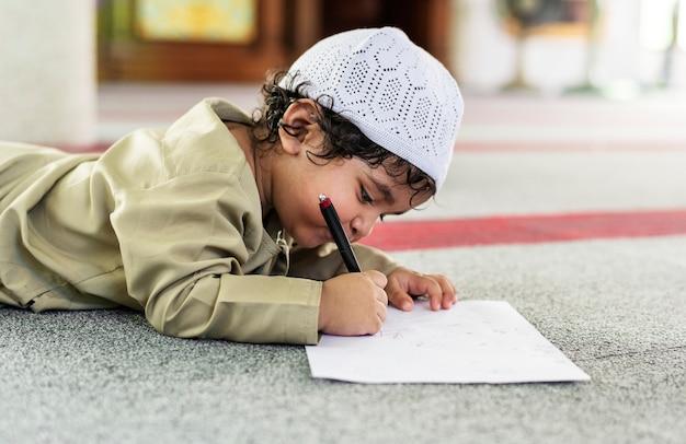 Chico musulmán aprendiendo en una mezquita