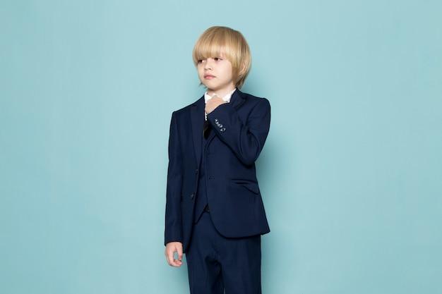 Un chico de negocios lindo vista frontal en traje clásico azul posando moda de trabajo empresarial