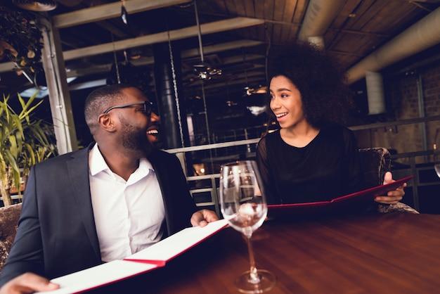 El chico negro y la chica vinieron al restaurante.