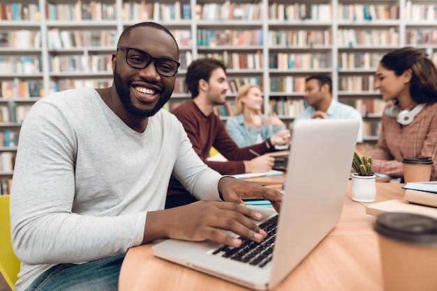Chico negro en la computadora portátil en la biblioteca de la escuela.