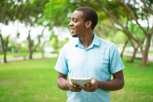 Chico negro guapo alegre mirando a un lado mientras usa un gadget moderno.