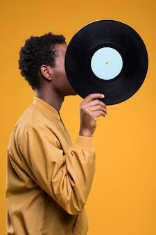 Chico negro posando con vinilo