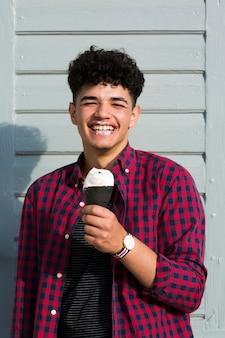 Chico negro riendo en camisa a cuadros con helado