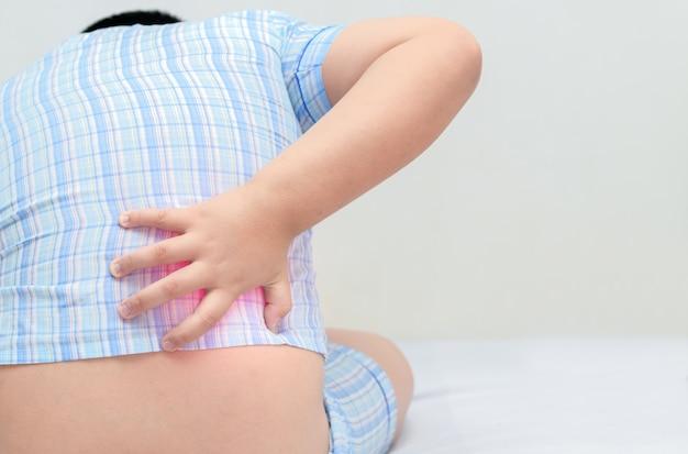 Chico obeso que sufre de dolor de espalda