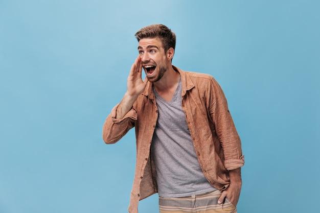 Chico de ojos grises positivo con barba fresca en camisa de moda y pantalones beige a rayas mirando a otro lado y gritando en la pared azul