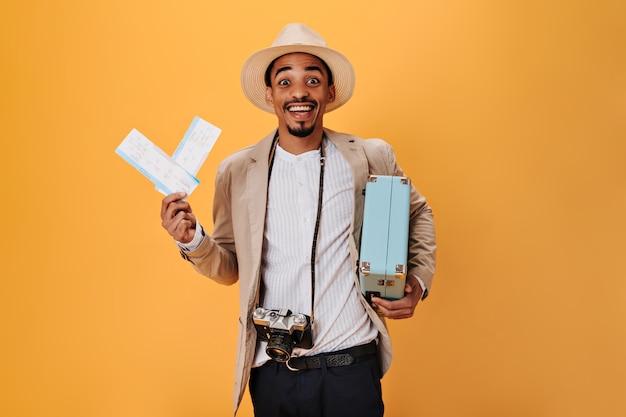 El chico de ojos marrones está feliz por sus futuras vacaciones, tiene boletos y maleta. hombre encantador disfruta de viaje