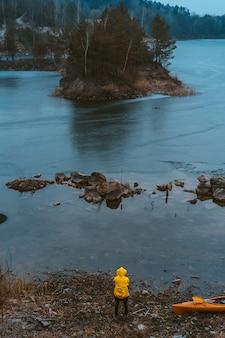 El chico está parado en el lago congelado.