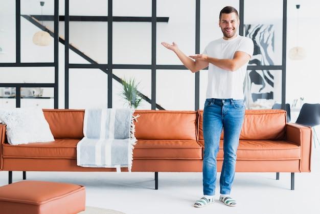 Chico parado y mostrando su sala de estar