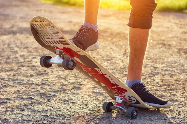 El chico se para en una patineta está en la carretera hermosa tonificación.