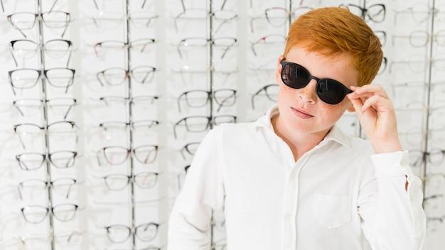 Chico pecosa con anteojos negros posando en tienda de óptica