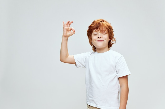 Chico pelirrojo alegre gesticulando con su mano sonrisa ojos cerrados camiseta blanca studio