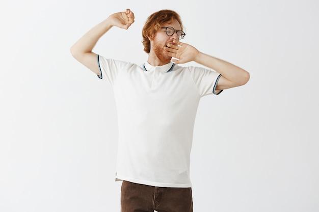 Chico pelirrojo barbudo relajado posando contra la pared blanca con gafas